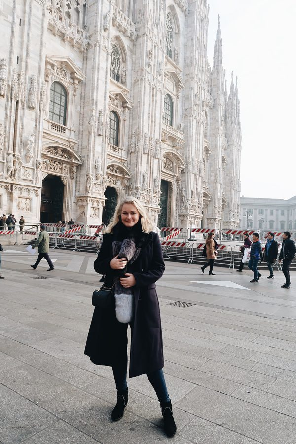 Lorna weightman wearing a long navy coat, jeans and boots in front of a large cathedral in Milan