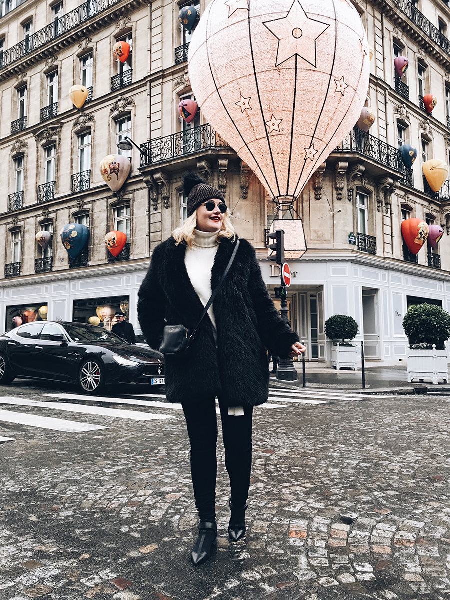Lorna Weightman wearing black faux fur jacket, wool hat, jeans and boots pictured on a street in front of a shop door in central Paris