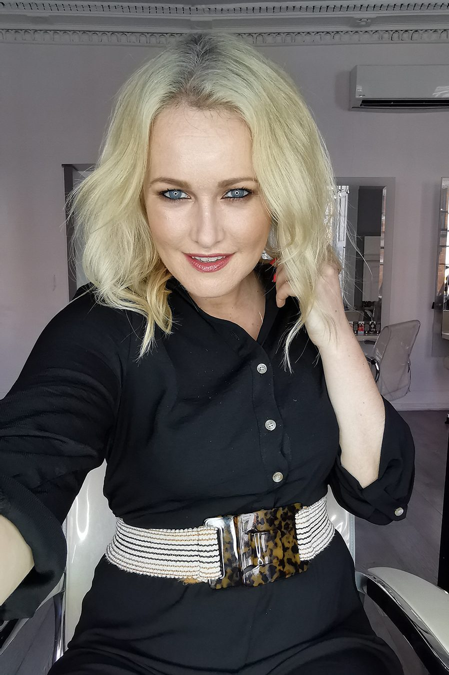 Lorna Weightman in black jumpsuit in front of mirror