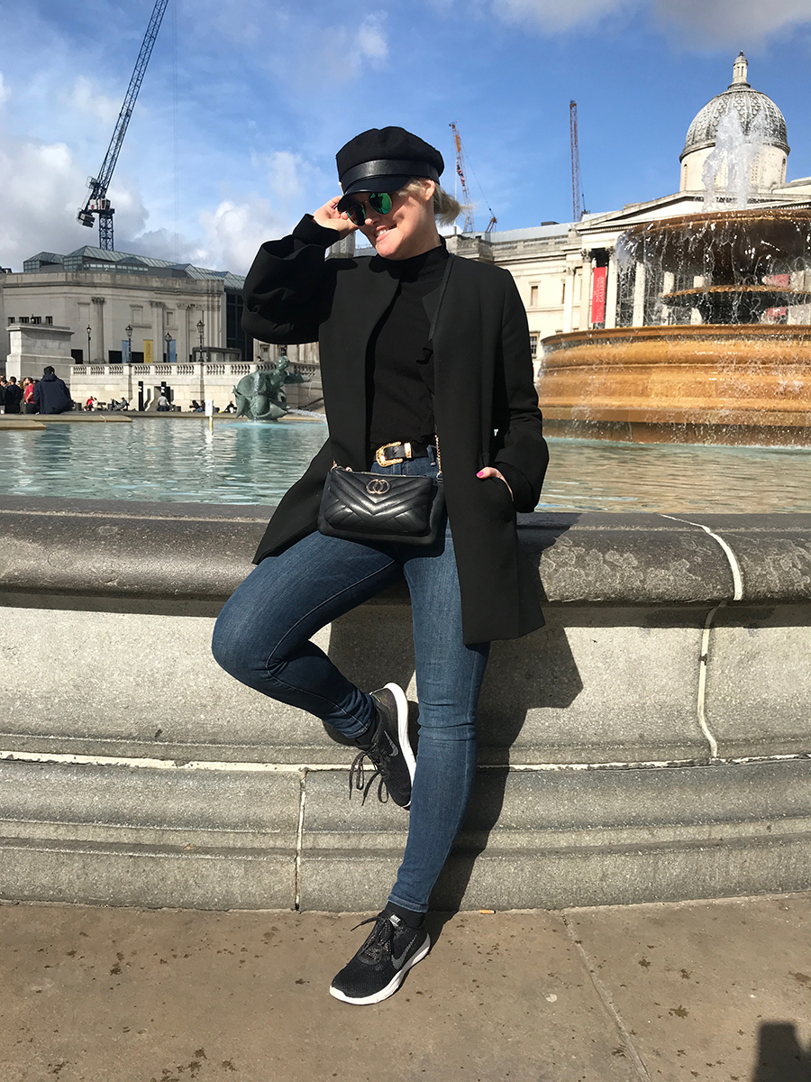 Lorna Weightman wearing black coat, jeans and black trainers, in front of Trafalgar square London