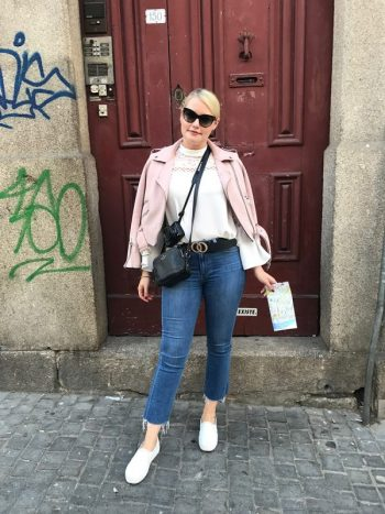 Lorna Weightman pictured wearing pink jacket, jeans also wearing sunglasses and holding a map pictured in front of a red door