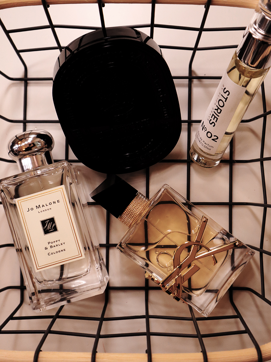 Image of four fragrance bottles in a wire basket for decoration