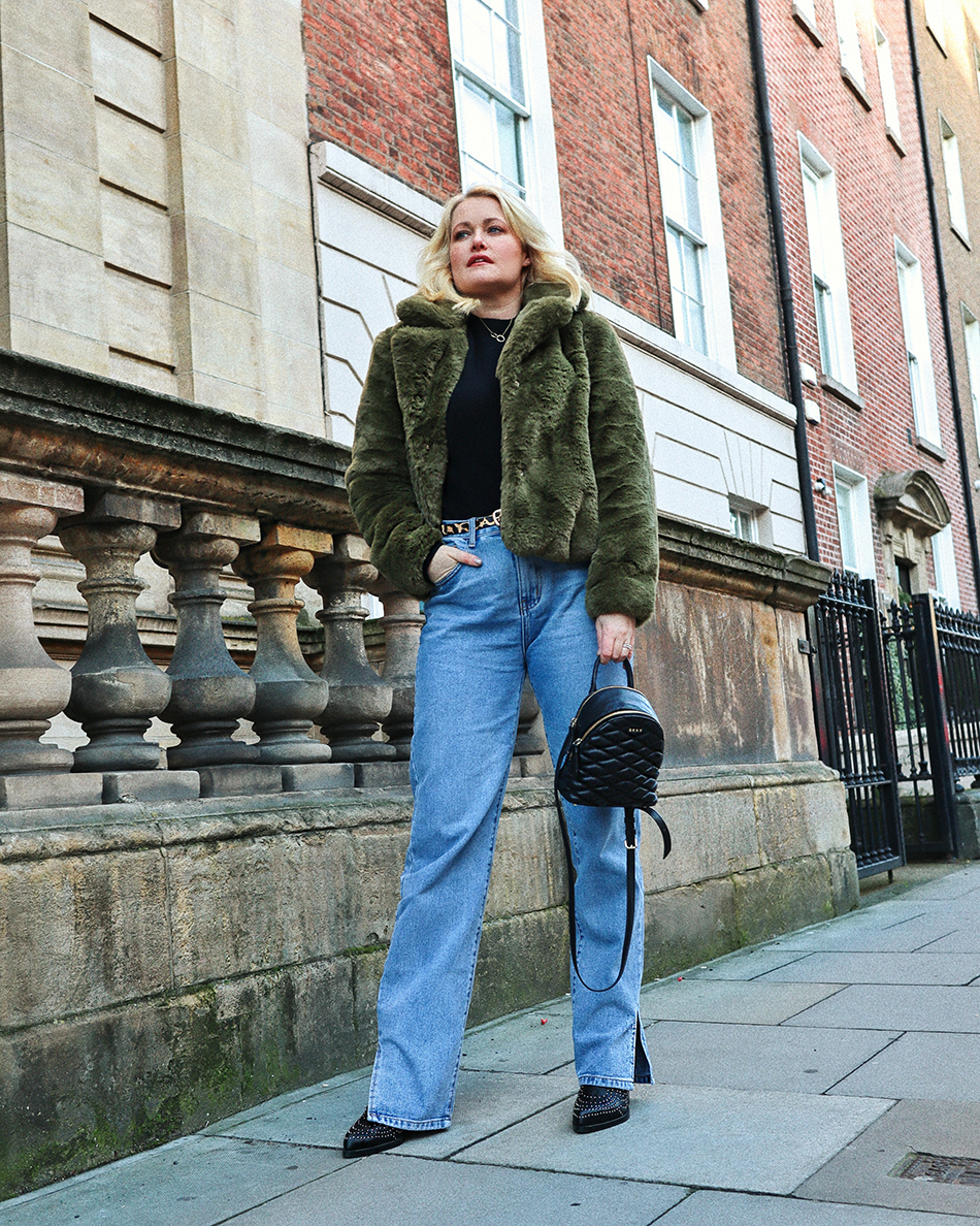 Lorna Weightman wearing green faux fur short jacket, black knitted jumper underneath, blue denim jeans with black ankle boots with studs. Holding a black bag
