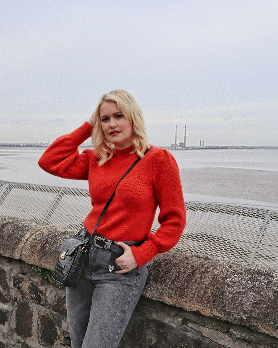 Lorna Weightman pictured in front of the sea wearing a red jumper and grey jeans holding a black bag