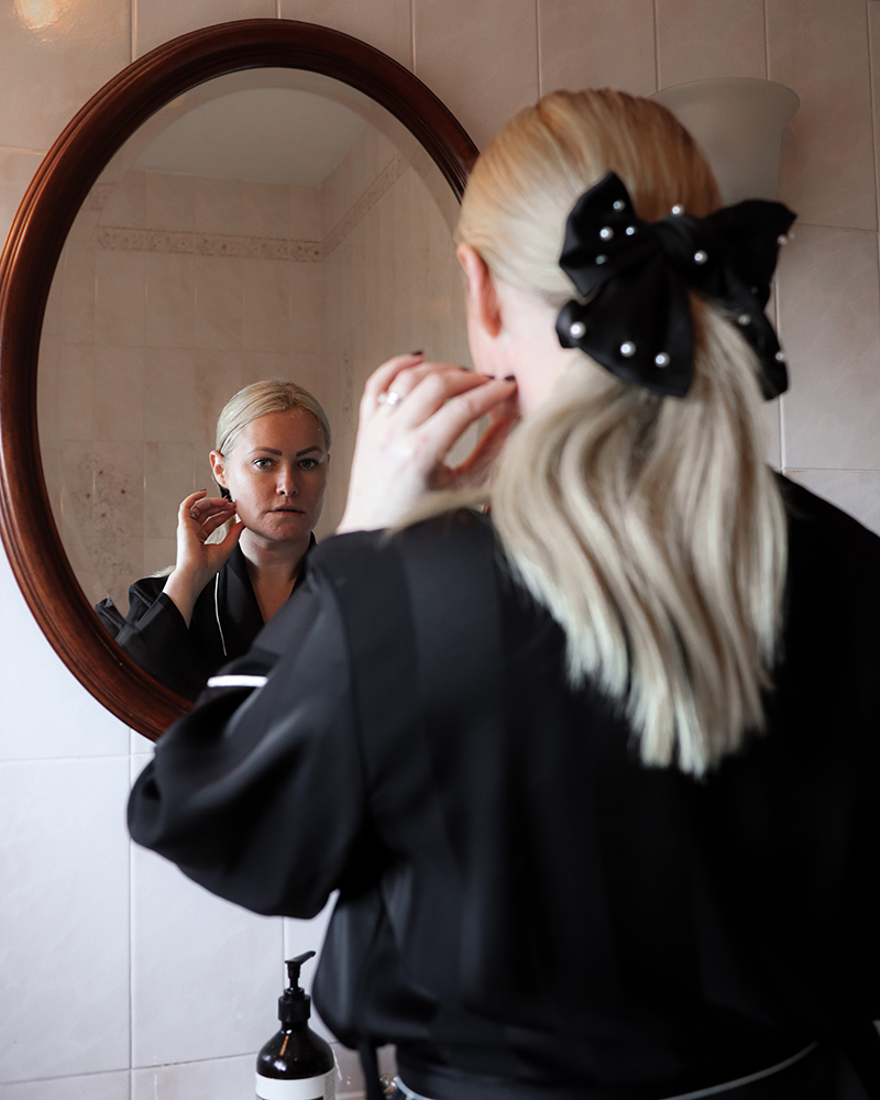 Image of Lorna Weightman looking into a mirror wearing a black robe and bow in a ponytail