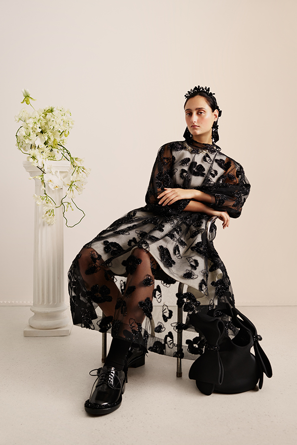 Image of female sitting wearing black chiffon dress with a floral decoration, black shoes and black headband