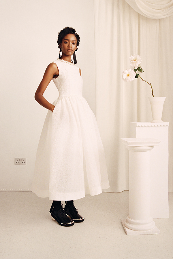 Image shows female wearing white dress with black shoes next to a tall white table with a white flower on top