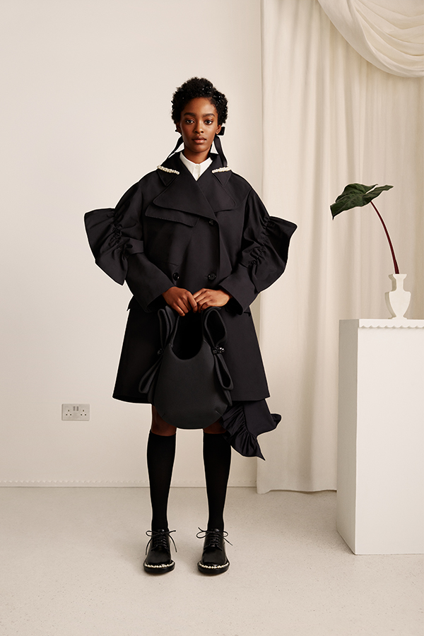 Image shows female wearing black coat, holding a black bag next to a white table with plant