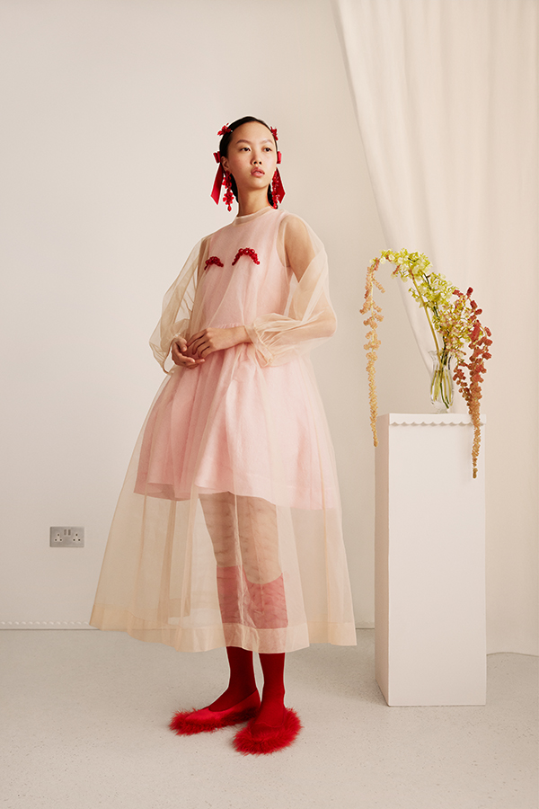 Image of female standing wearing cream tulle dress with red decoration and red socks and shoes