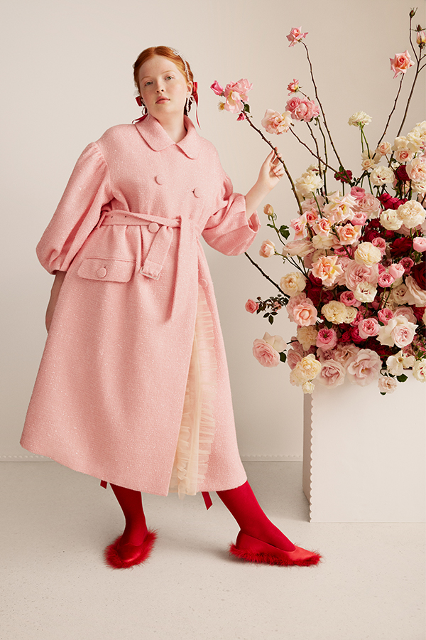 Image of female standing wearing a pink coat, red socks and red shoes