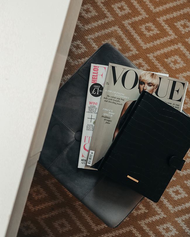 Image of grey box seat with magazines and a black personal diary placed on top