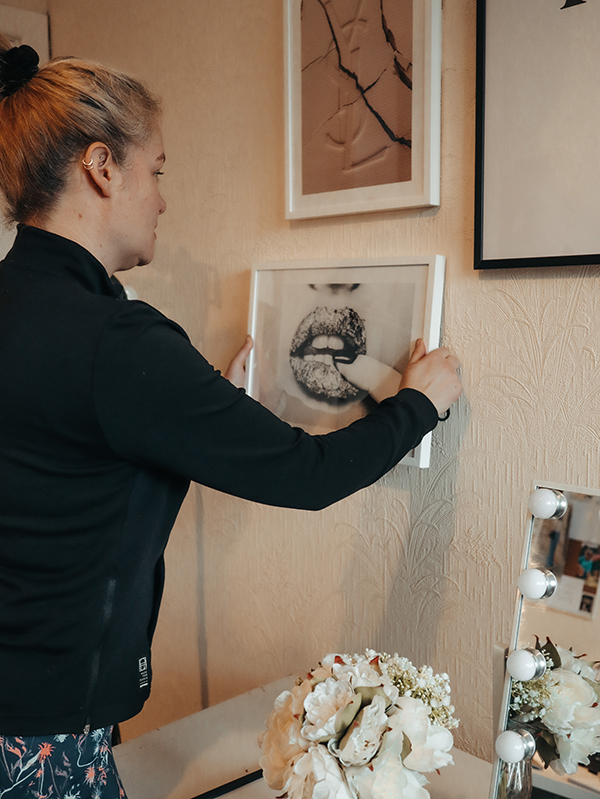 Image of a piece of art being hung on a wall as part of building a gallery wall