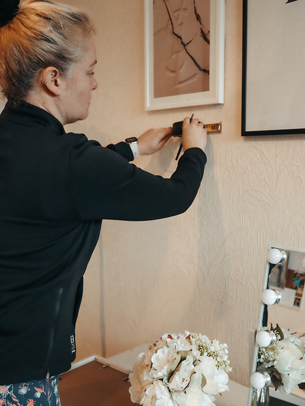 Measuring a wall with a tape measure as part of how to build a gallery wall