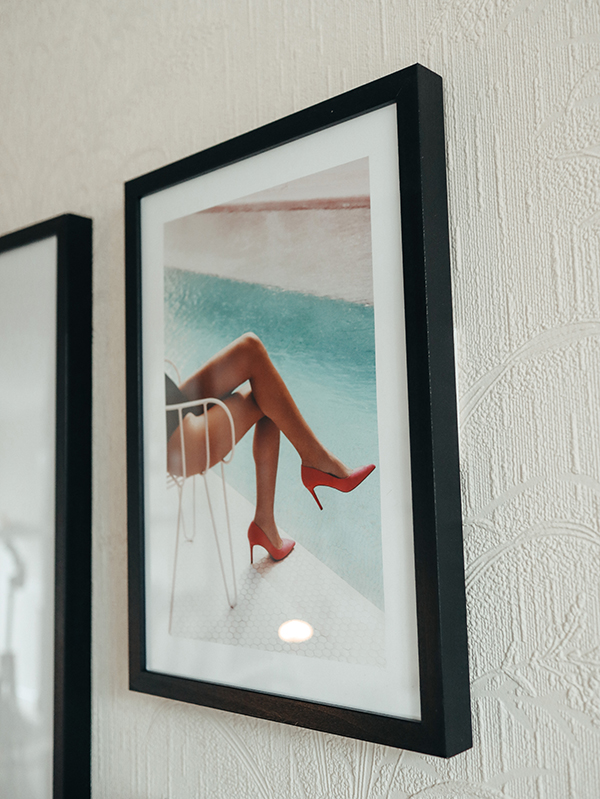 image of female showing legs wearing pink high heels and sitting by a pool as part of a gallery wall